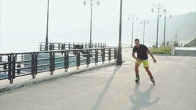 Junge sportliche Mannrollschuhlaufen auf Sommerufergegend stock video