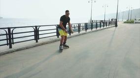 Junge sportliche Mannrollschuhlaufen auf Sommerufergegend stock video footage