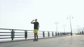 Junge sportliche Mannrollschuhlaufen und -getränk wässern von der Flasche auf Ufergegend stock video