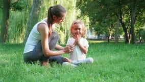 Junge sportliche Mutter, die ihre kleine nette Tochter tut Yogaübung trainiert stock video