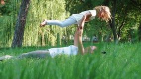 Junge sportliche Mutter, die ihre kleine nette Tochter tut Yogaübung trainiert stock video footage