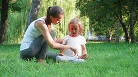 Junge sportliche Mutter, die ihre kleine nette Tochter tut Yogaübung trainiert stock footage