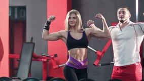 Junge sportliche Paare, die Muskel und Training in der Turnhalle zeigen stock video