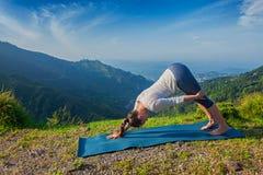 Junge sportliche Sitzfrau, die Yoga oudoors in den Bergen tut Stockfotografie