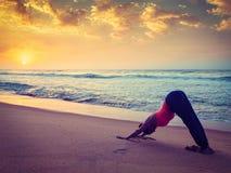 Junge sportliche Sitzfrau, die Yoga am Strand auf Sonnenuntergang tut Lizenzfreie Stockfotos