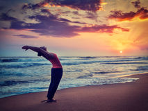 Junge sportliche Sitzfrau, die Yoga Sun-Gruß Surya Namaskar tut Stockbild