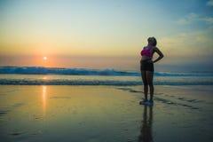 Junge sportliche und müde Afroamerikanerläuferfrau, die weg atmen erschöpft nach laufendem Training an den schönen Strandsonnen a stockbild