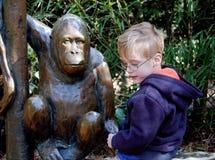 Junge spricht mit Affe-Statue Lizenzfreie Stockfotografie
