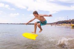 Junge springt in den Ozean mit seinem Boogiebrett Lizenzfreie Stockbilder
