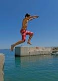 Junge springt in Meer Stockfotos