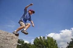 Junge springt vom Felsen. stockbild