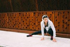 Junge städtische Eignungsfrau, die Adduktoren ausdehnt Stockbilder