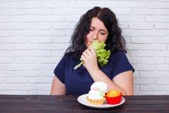 Junge störten die überladene Frau, die von den Diäten gebohrt wurde, die gesundes Lebensmittel essen stockfotografie