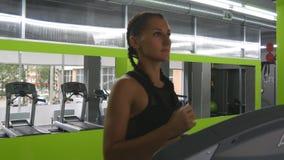Junge starke Frau mit perfektem Eignungskörper in der Sportkleidung, die auf Tretmühle in der Turnhalle läuft Mädchen, das währen stock video