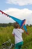 Junge startet in den blauen Himmel einen Drachen lizenzfreie stockfotografie