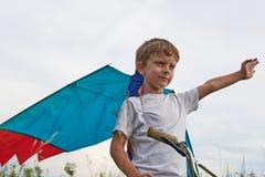 Junge startet in den blauen Himmel einen Drachen lizenzfreie stockfotos