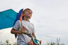 Junge startet in den blauen Himmel einen Drachen stockfotos