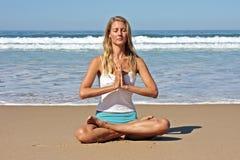 Junge stattliche Frau, die auf dem Strand meditiert Lizenzfreie Stockbilder