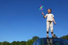 Junge steht auf Dach des Autos und hält Windmühle an Stockbild