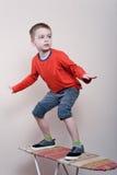 Junge steht auf einem Brett Lizenzfreie Stockbilder