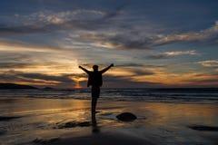Junge steht auf Strand mit den Armen, die unter einem drastischen Sonnenunterganghimmel ausgestreckt werden Lizenzfreie Stockbilder