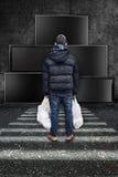 Junge steht mit Plastiktasche in den Händen Stockfotografie