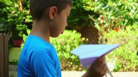 Junge stellt ein Papierflugzeug an stock video footage