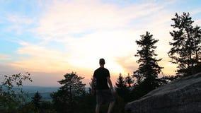 Junge Stellung, feiern auf Steinfelsen in der tschechischen Landschaft bei Sonnenuntergang stock video