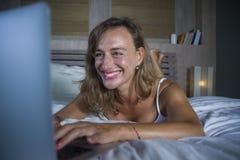 Junge stilvolle attraktive und schöne kaukasische Frau 30s, die auf Bett nachts im Hauptschlafzimmer unter Verwendung des Interne Lizenzfreie Stockfotografie