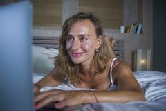 Junge stilvolle attraktive und schöne kaukasische Frau 30s, die auf Bett nachts im Hauptschlafzimmer unter Verwendung des Interne Lizenzfreies Stockbild