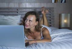 Junge stilvolle attraktive und schöne kaukasische Frau 30s, die auf Bett nachts im Hauptschlafzimmer unter Verwendung des Interne Lizenzfreie Stockbilder