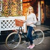 Junge stilvolle Frau auf einem Weinlesefahrrad Stockbilder