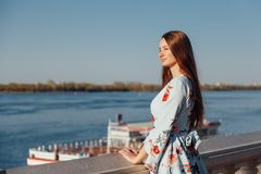 Junge stilvolle Frau in der empfindlichen blauen Kleiderstellung auf dem Strand und im Genie?en des Sonnenuntergangs stockbild