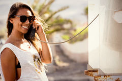 Junge stilvolle Frau an der Telefonzelle Telefongesprächsretrostil Lizenzfreie Stockfotografie