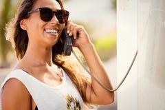 Junge stilvolle Frau an der Telefonzelle Telefongesprächsretrostil Lizenzfreies Stockfoto