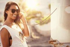 Junge stilvolle Frau an der Telefonzelle Telefongesprächsretrostil Lizenzfreie Stockbilder