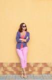 Junge stilvolle Frau, die gegen die Wand aufwirft Stockbilder