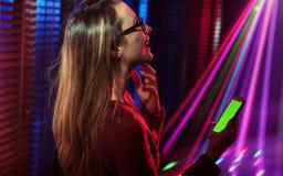 Junge stilvolle Frau, die Smartphone an der Disco verwendet lizenzfreie stockfotos