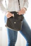 Junge stilvolle Frau, die Tampon von der Handtasche nimmt Stockbild
