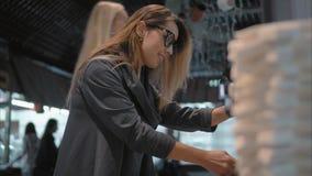Junge stilvolle Frau gießt sich ein Tee auf einem Gastronomiebereich stock footage