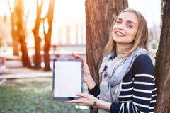 Junge stilvolle Frau Smilling hält digitale Tablette mit Kopienraum auf dem Schirm für Ihren Werbungsinhalt Recht weibliches s Lizenzfreies Stockbild