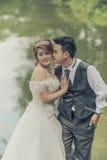 Junge stilvolle Modepaare Asiens, die auf Natur aufwerfen Stockfotografie