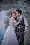Junge stilvolle Modepaare Asiens, die auf Natur aufwerfen Stockfoto