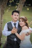 Junge stilvolle Modepaare Asiens, die auf Natur aufwerfen Stockbild