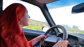 Junge stilvolle moslemische Frau in hijab Autofahren stock footage