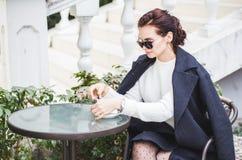 Junge stilvolle Schönheit in der Sonnenbrille, die in einem trinkenden Kaffee des Cafés im Freien sitzt lizenzfreie stockfotos