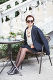 Junge stilvolle Schönheit in der Sonnenbrille, die in einem trinkenden Kaffee des Cafés im Freien sitzt lizenzfreie stockbilder