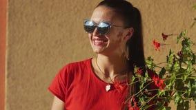 Junge stilvolle sexy Frau im roten Sommerkleid, das auf Terrasse im Hotel, langes schwarzes Haar, Sonnenbrille, ethnische Ohrring stock video