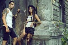 Junge stilvolle tätowierte Paare in den schwarzen kurzen Hosen, die an der Spalte des alten ruinierten Hauses stehen lizenzfreie stockfotografie
