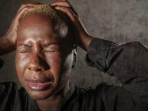 Junge stilvolle traurige und deprimierte afroe-amerikanisch schwarze Frau, die in der Verzweiflung halten Haupt mit den Händen si Stockfoto